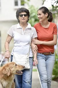 Woman assisting older bind woman with cane and service dog