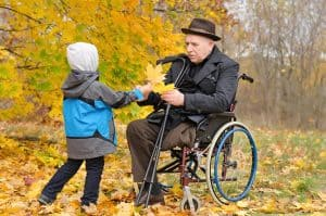 Young child giving leaves to older man in a wheelchair